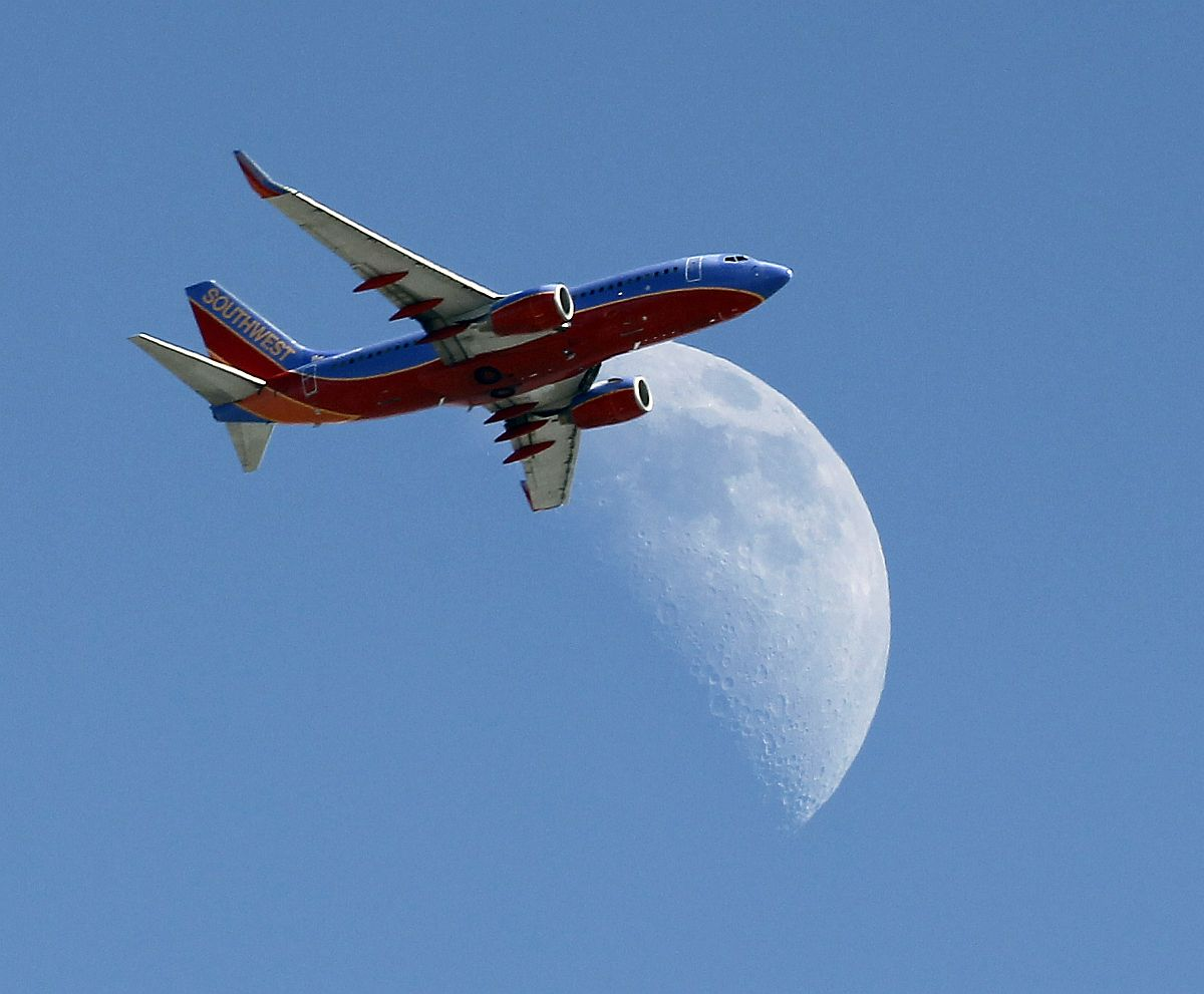 A Southwest Air flight WN2921 from San Antonio plane crosses over a crescent moon as it passes over Whittier, Calif. en route to the Los Angeles Airport (LAX) on Labor Day, Monday, Sept. 1, 2014. (AP Photo/Nick Ut)