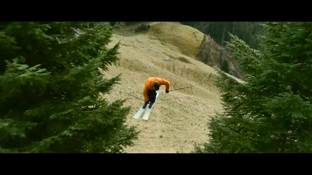 Кандид Тове спускается на лыжах по горе без снега